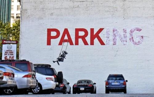 Graffitti de Banksy: niña en columpio en un PARK-ing